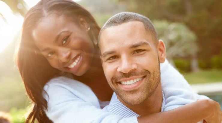 A romantic black man carrying a black woman