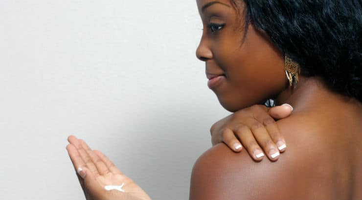 Black woman applying lotion