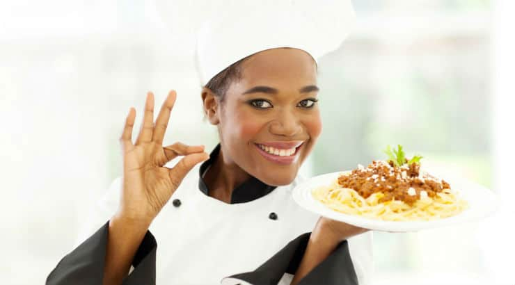Black female chef holding a plate of pasta