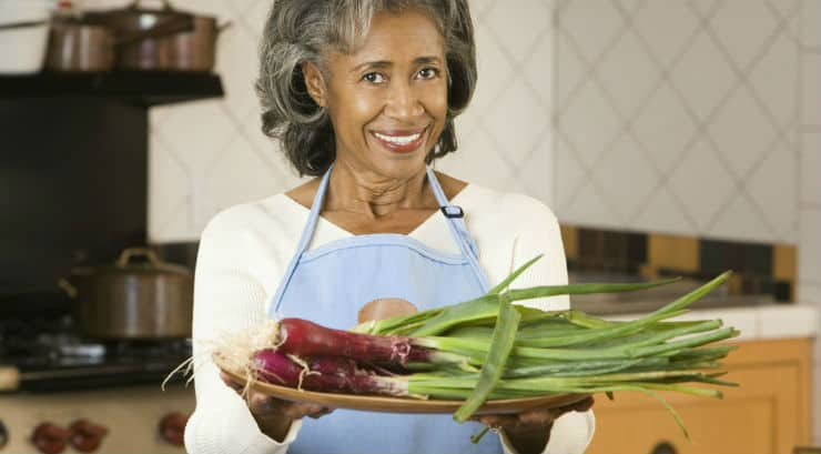 Elderly black woman holding a plate of vegetables