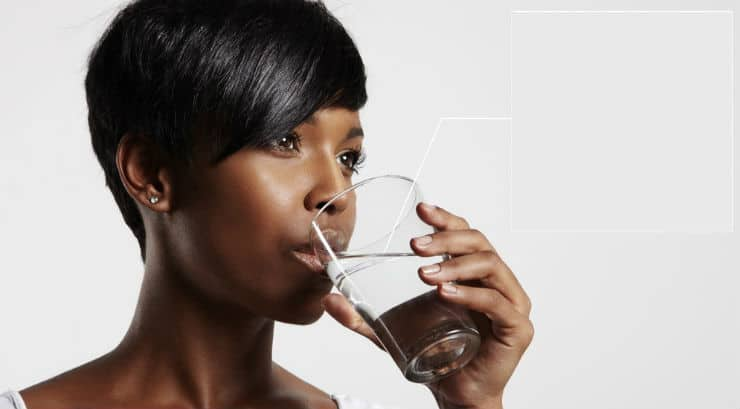 A black woman drinking a glass of water