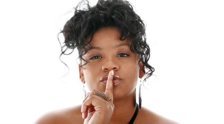 A black woman doing the hush gesture due to her office romance