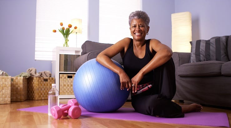 A happy and motivated African American woman with workout equipment