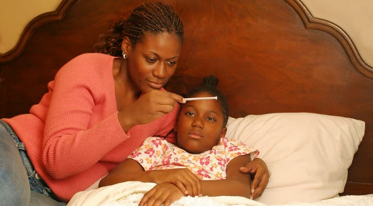 A black mother taking the temparature of her sick daughter