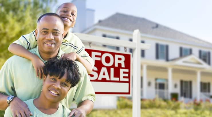 A black family infront of a for sale sign