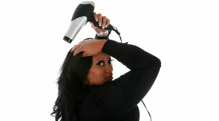 A black woman blowdrying her hair