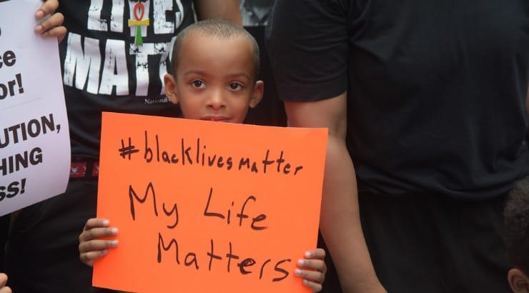 A small black boy holding a BLM placard