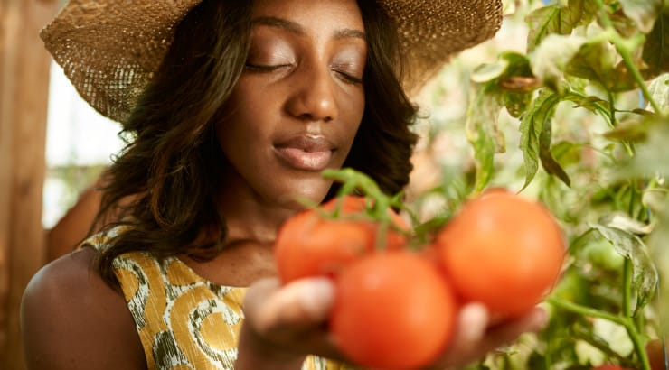 A black woman holding fresh tomatoes