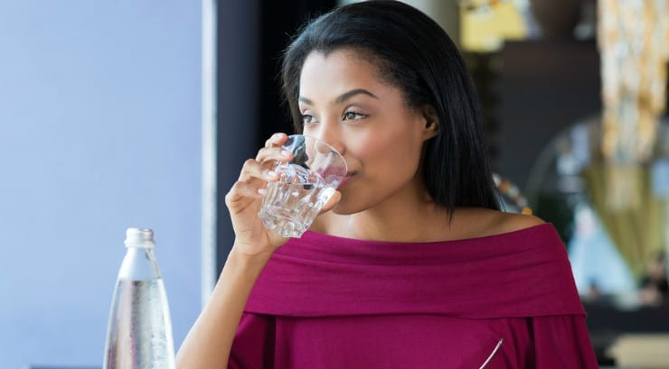 An African American woman drinking a glass of water