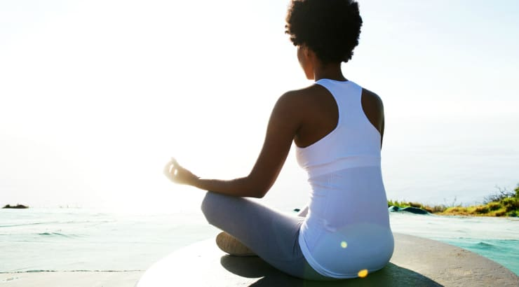Black woman showing consistency is important when getting into yoga