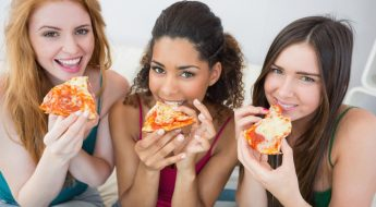 Image of Women eating pizza on a sofa at home