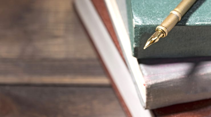 Books on a wooden table with a fountain pen