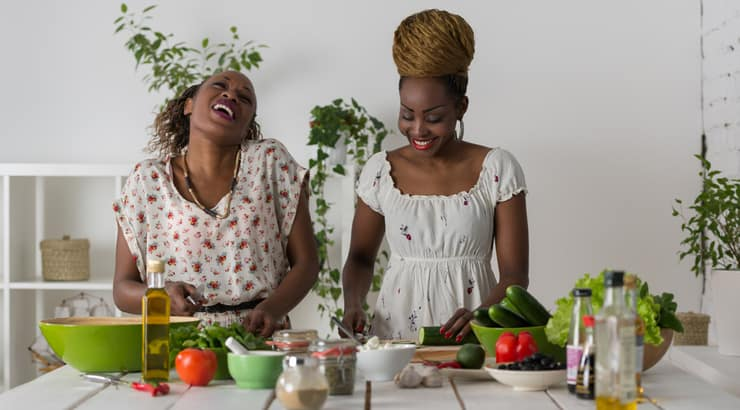 Black women in kitchen cooking and laughing
