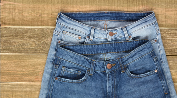 Two Pairs of High Waist Women Jeans on Wooden Background