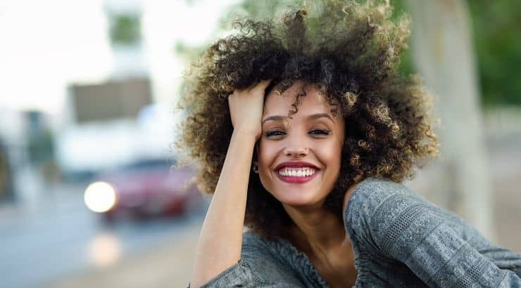 Using a heat protectant is the first step to preparing curly hair for flat irons.