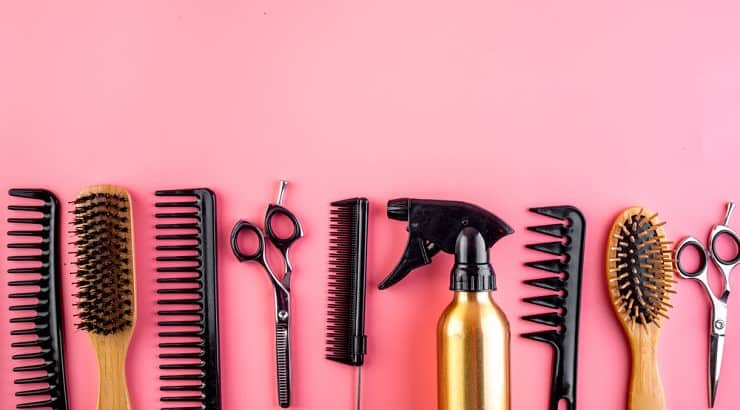 A detangling brush, spray bottle, and hair clips are tools that make detangling natural hair easier.